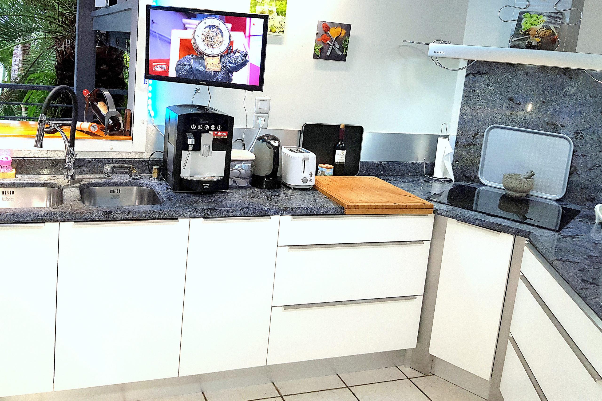 Cuisine partagée avec plaques induction, tv et machine à café malongo donnant sur le jardin tropical