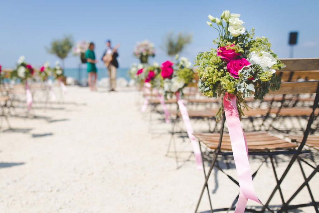 Wedding ceremony on the beach with bouquets on the chairs and musicians