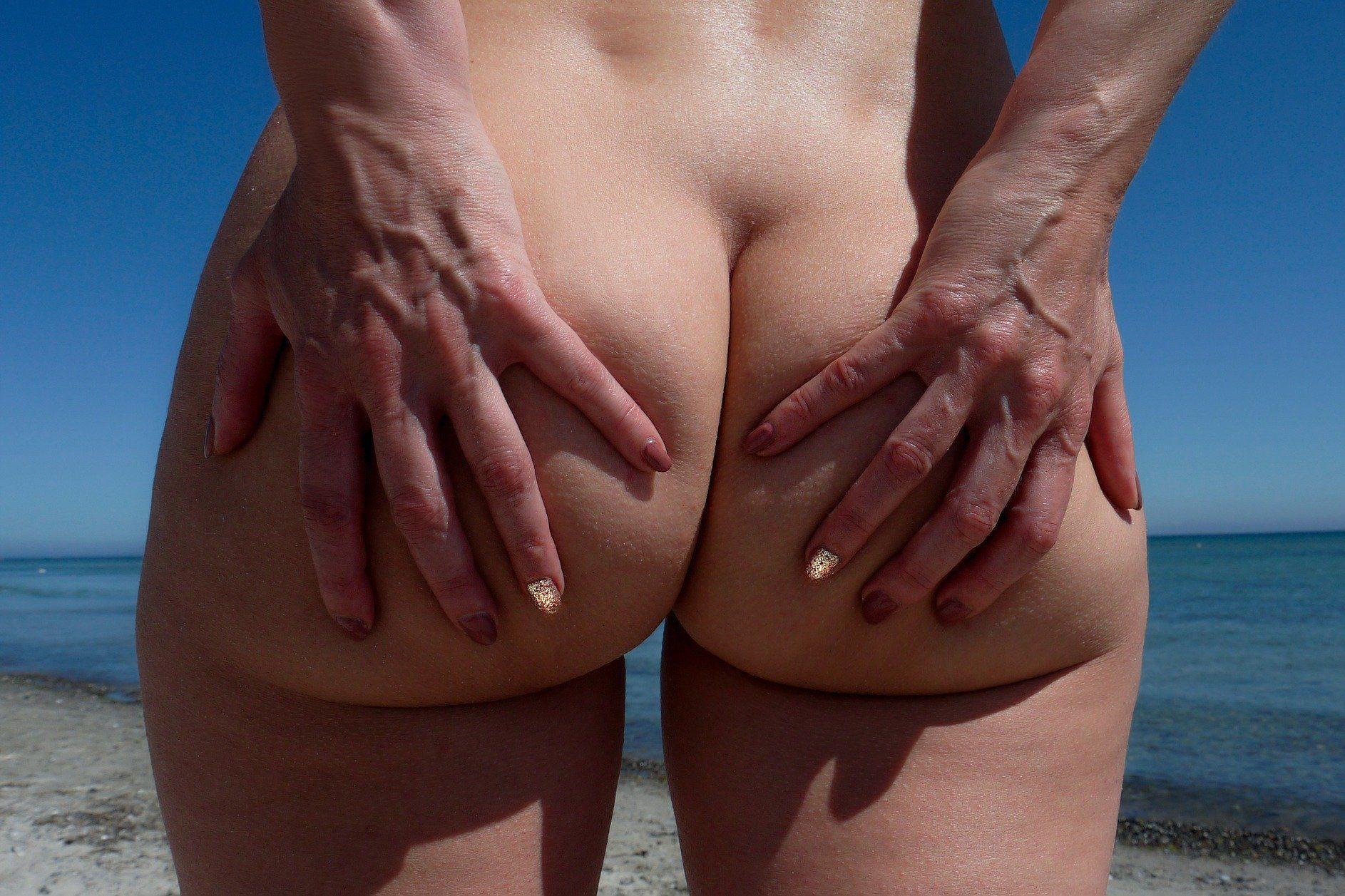 Femme nue de dos avec les mains sur les fesses